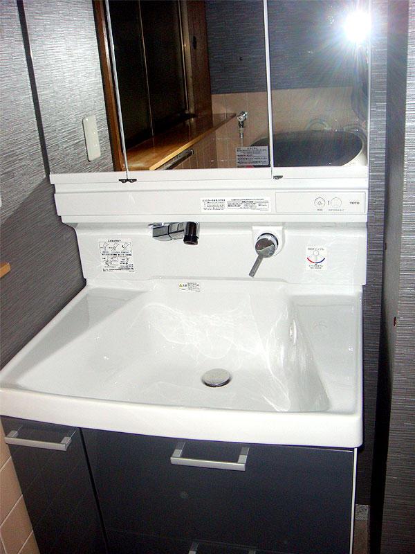 収納力を上げた洗面化粧台と落ち着いた雰囲気のクロス